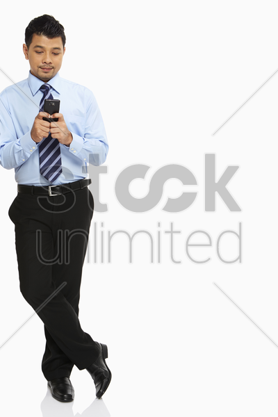 businessman leaning against a wall, text messaging stock photo