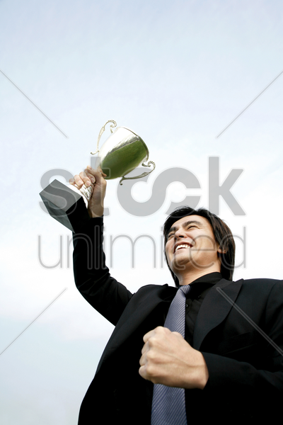 businessman lifting up his trophy stock photo