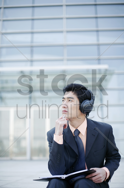 businessman listening to music on the headphone stock photo