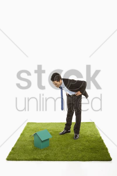 businessman looking at a cardboard house stock photo