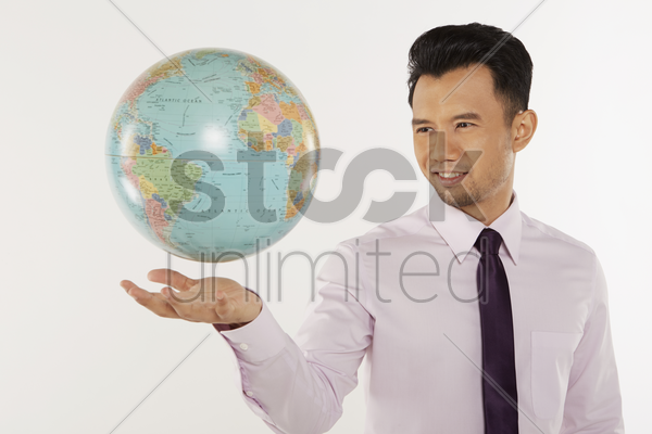 businessman looking at a floating globe stock photo