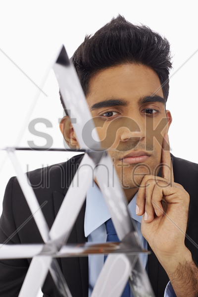 businessman looking at a pyramid of cards stock photo
