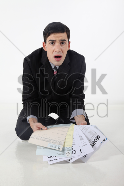 businessman looking at all his loans stock photo