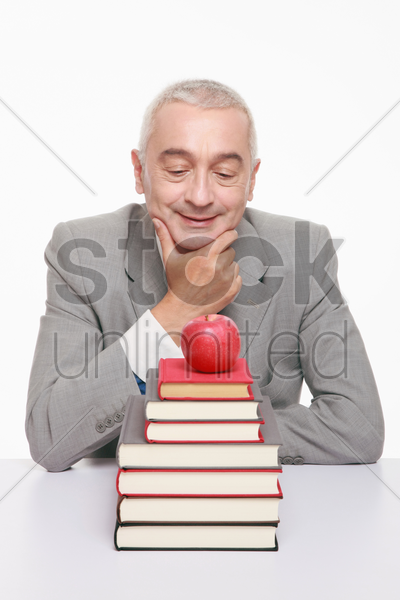 businessman looking at apple on a stack of books stock photo