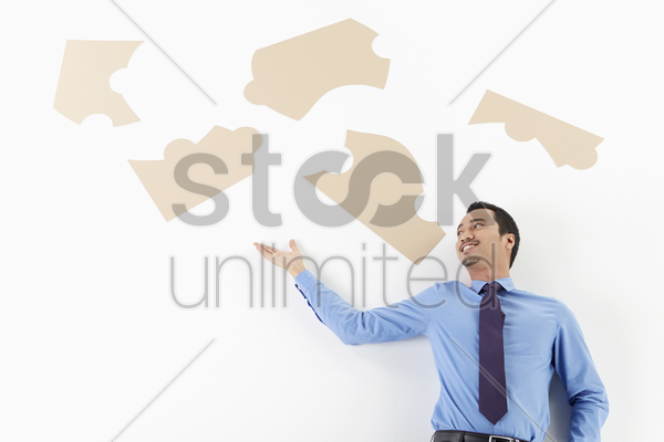 businessman looking at puzzle pieces stock photo