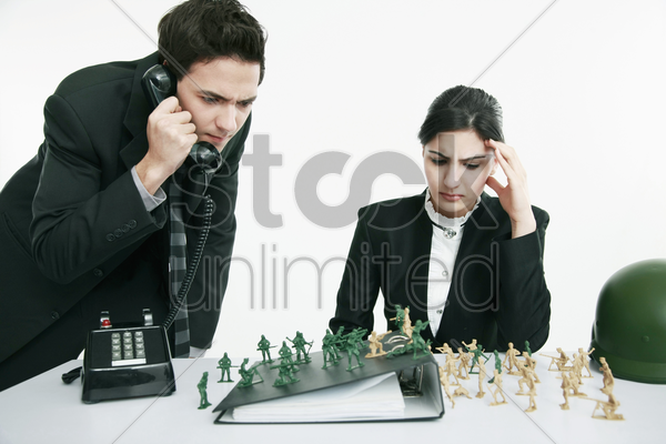 businessman looking at toy soldiers while talking on the phone, businesswoman frowning stock photo