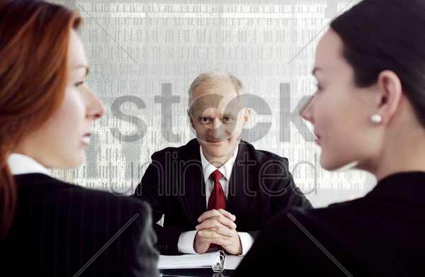 businessman looking at two businesswomen stock photo