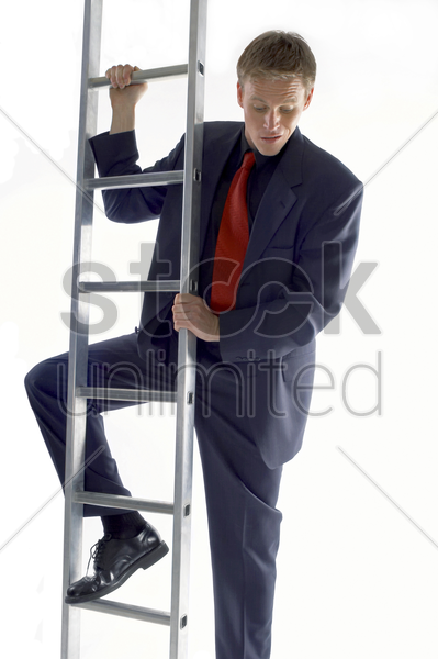businessman looking scared climbing up the ladder stock photo