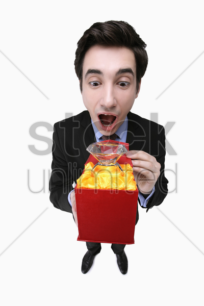 businessman looking shockingly at a gigantic diamond ring stock photo