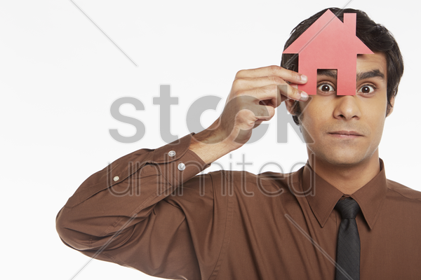 businessman looking through a cut out house stock photo