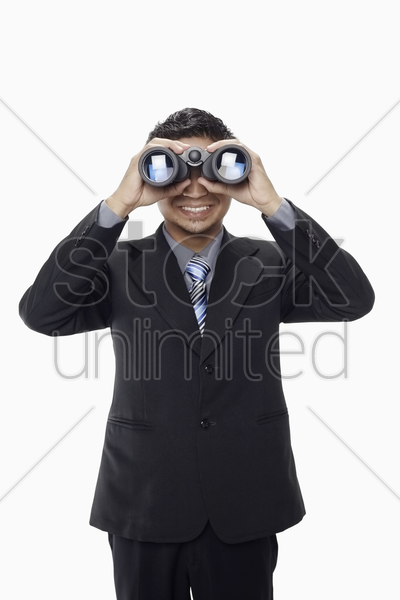 businessman looking through binoculars stock photo