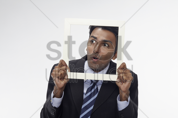 businessman looking through cutout paper frame stock photo