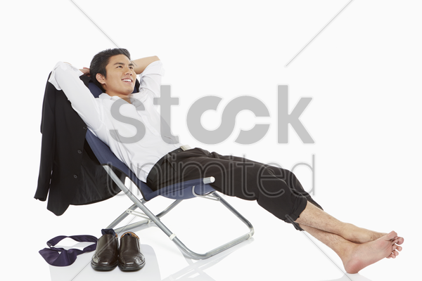 businessman lying on a chair, smiling stock photo