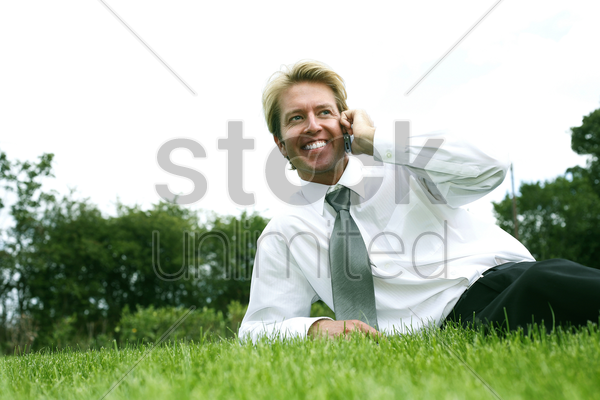 businessman lying on the field talking on the phone stock photo