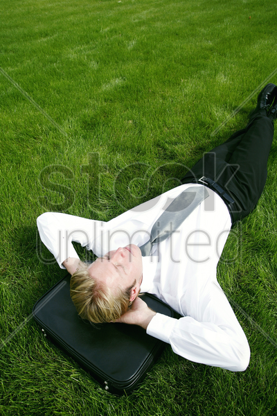 businessman lying on the field with his head on the briefcase stock photo