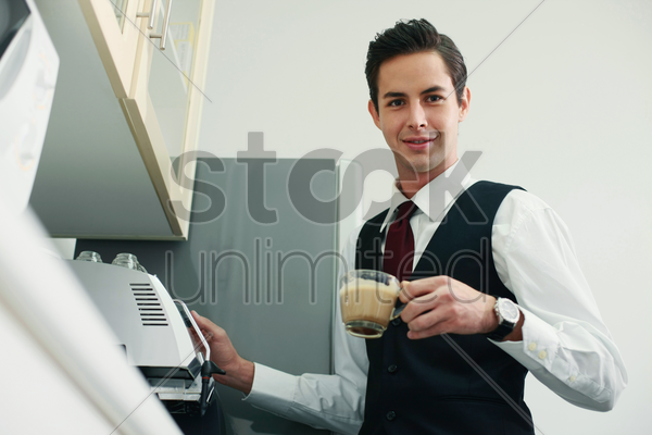 businessman making coffee in the office pantry stock photo