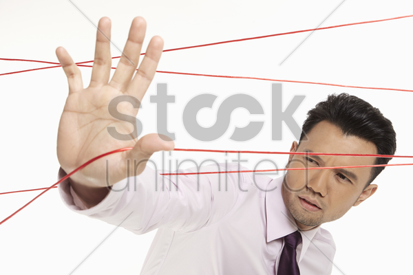 businessman making his way through tangled wires stock photo