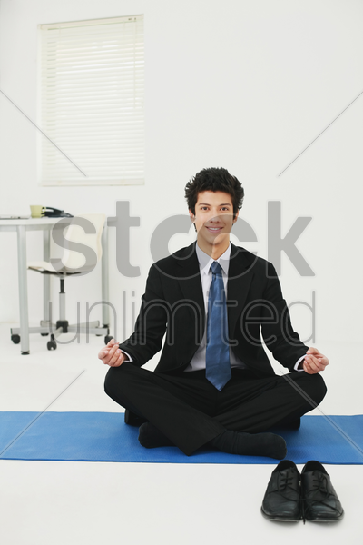 businessman meditating in office stock photo