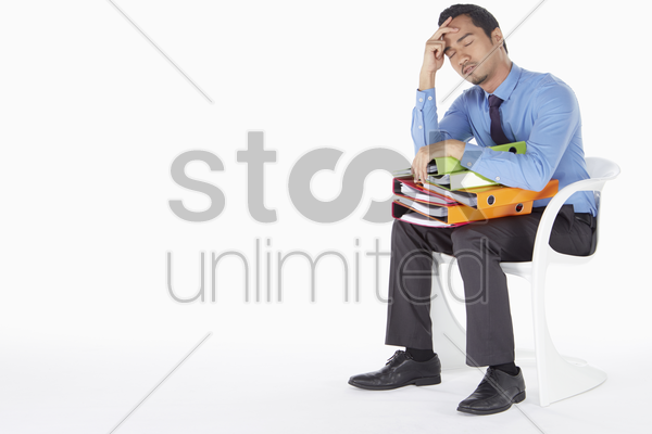 businessman napping on the chair with folders on lap stock photo
