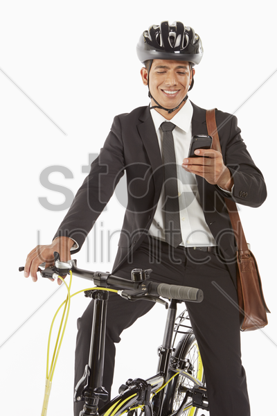 businessman on bicycle reading text message stock photo