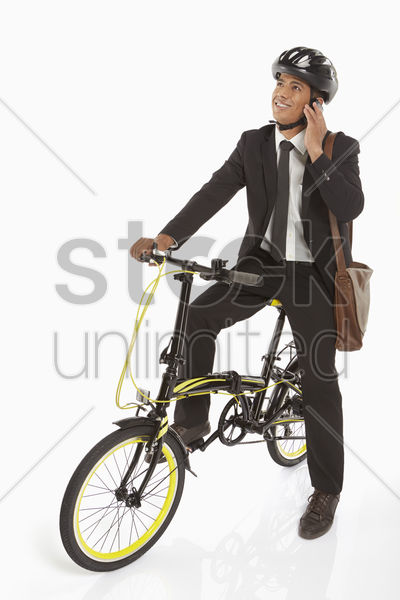 businessman on bicycle talking on the phone stock photo