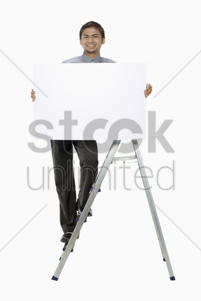 businessman on ladder holding blank placard stock photo