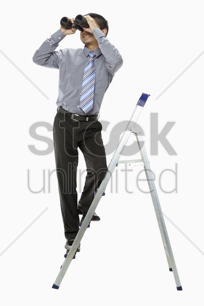 businessman on ladder looking through binoculars stock photo
