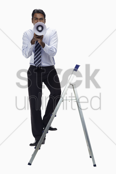 businessman on ladder screaming into megaphone stock photo