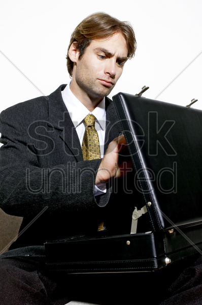 businessman opening his briefcase stock photo