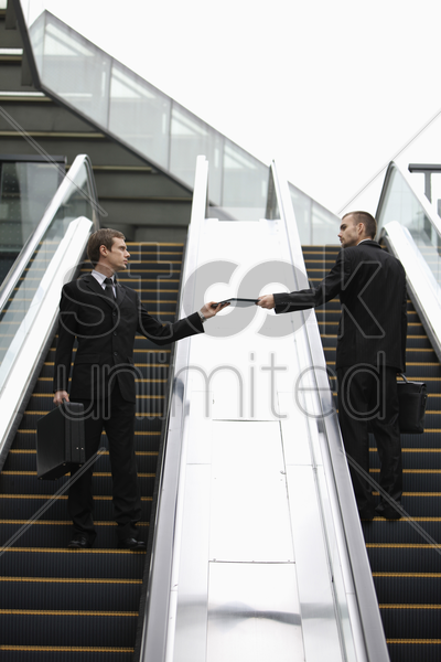 businessman passing a file to his colleague stock photo
