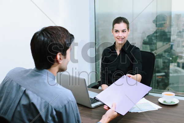 businessman passing document to businesswoman stock photo