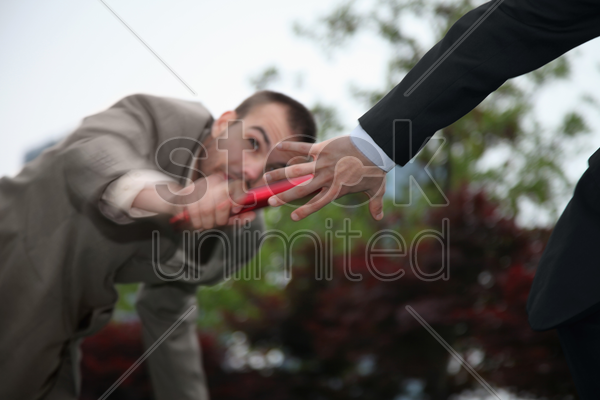 businessman passing the baton to his team mate stock photo