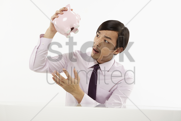businessman peeking into piggy bank stock photo