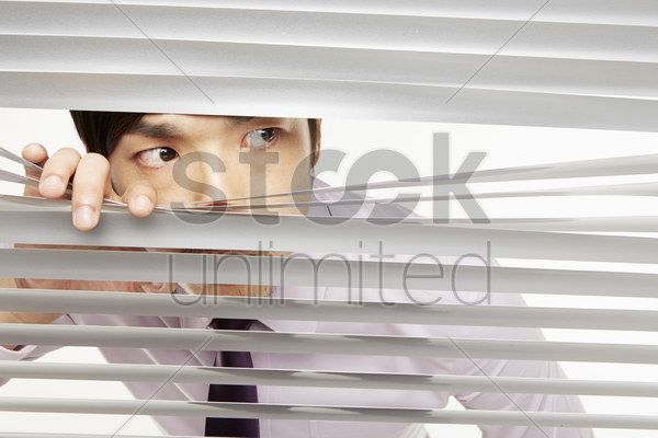 businessman peeking through window blinds stock photo