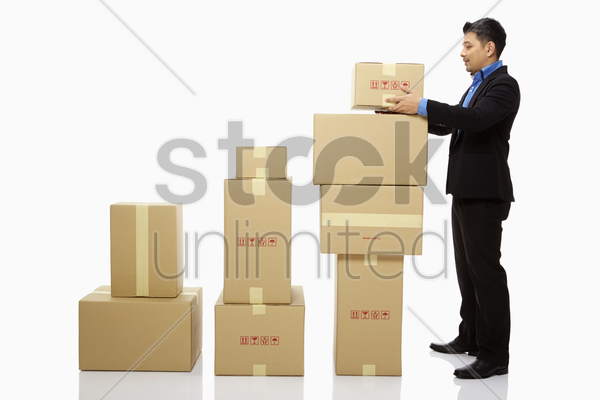 businessman placing a box on top of a stack of boxes stock photo
