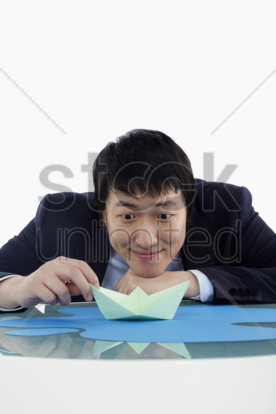businessman playing with a paper boat stock photo