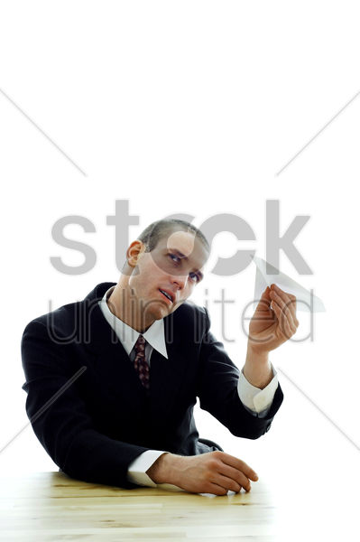 businessman playing with a paper plane stock photo