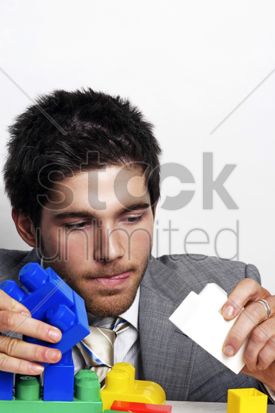 businessman playing with colourful plastic bricks stock photo
