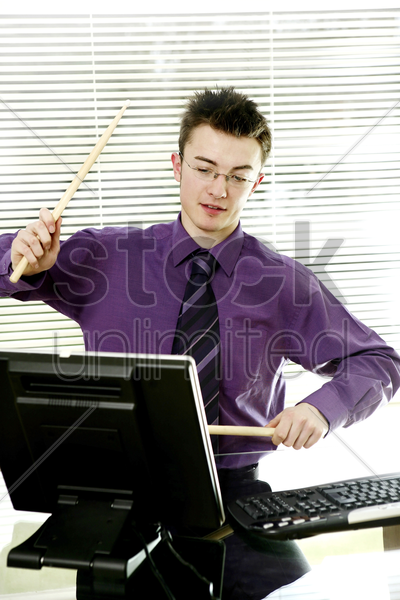 businessman playing with drum sticks stock photo