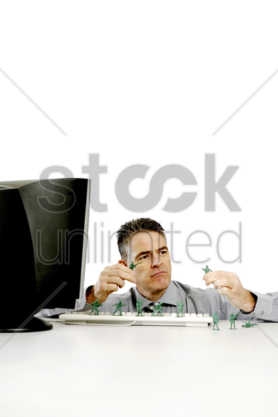 businessman playing with his toy soldiers stock photo