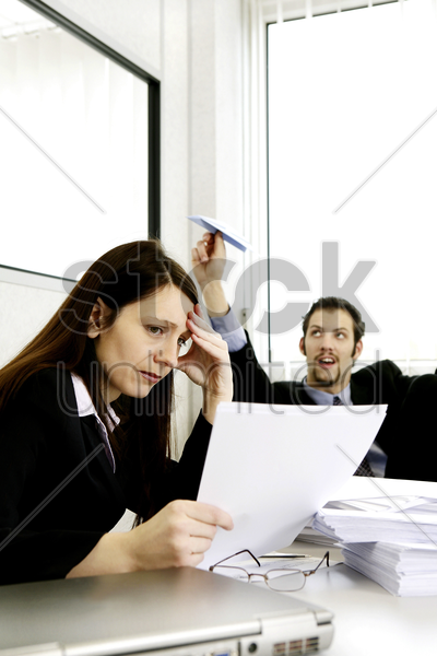 businessman playing with paper plane while his colleague is busy working stock photo