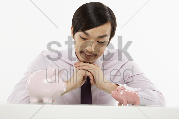 businessman playing with piggy banks stock photo