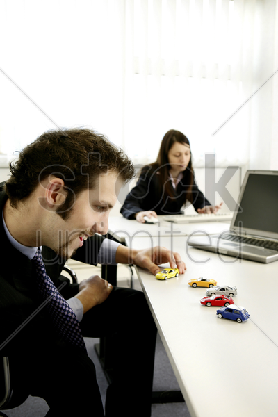 businessman playing with toy cars stock photo