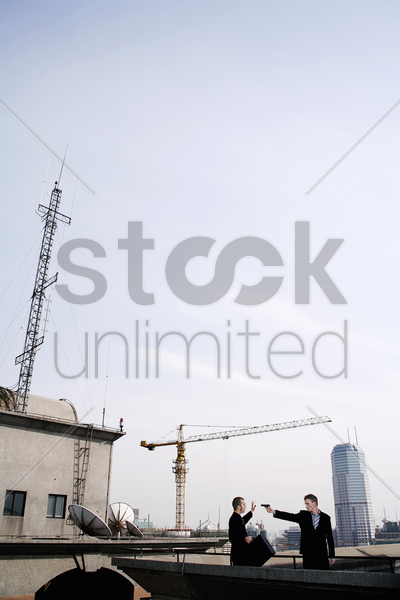 businessman pointing a gun at his partner stock photo
