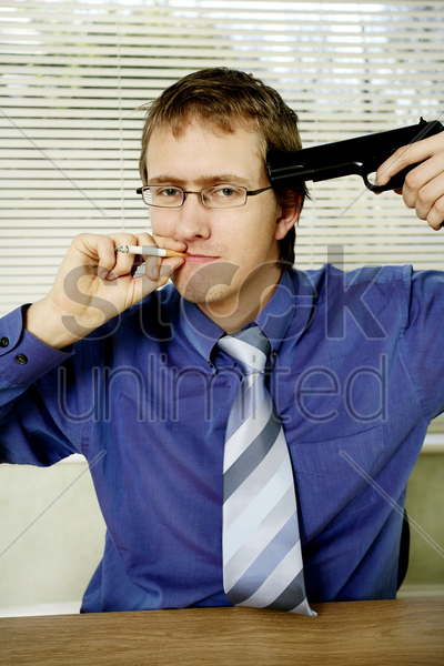 businessman pointing a pistol at himself while smoking cigarette stock photo