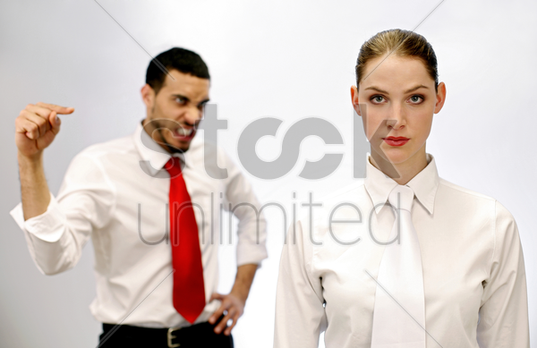 businessman pointing angrily at his female colleague stock photo
