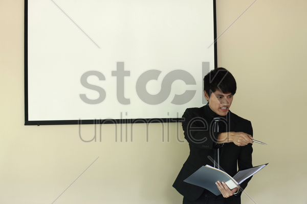 businessman pointing at the audience while giving presentation stock photo