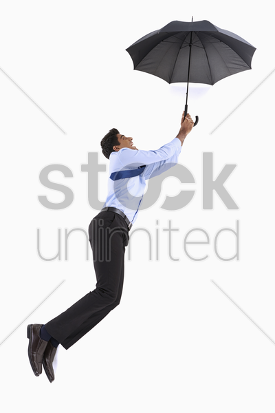businessman posing on the floor, holding an umbrella stock photo