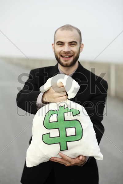 businessman posing with a bag of money stock photo