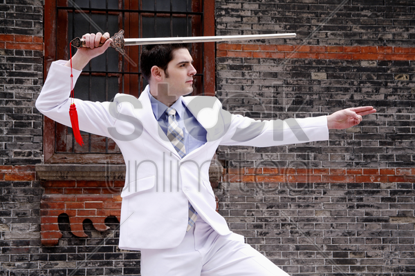 businessman practicing kung fu with a chinese sword stock photo
